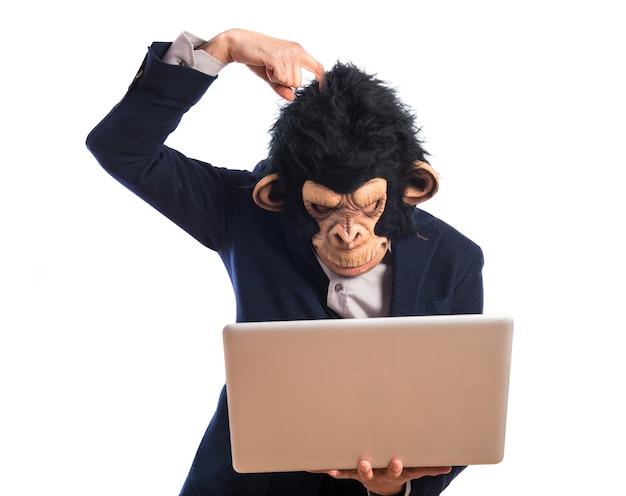 Uomo scimmia che ha dubbi con il suo computer portatile