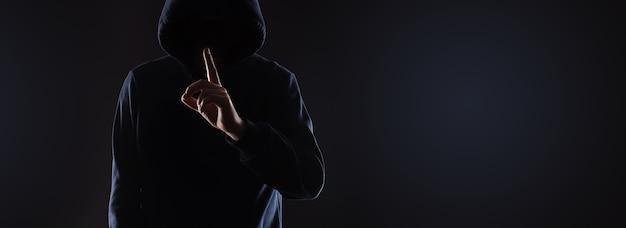 Uomo sconosciuto nella cappa che tiene il dito indice sulle labbra chiedendo silenzio. concetto segreto, mock-up panoramico con spazio per il testo