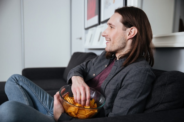 Uomo seduto a casa in casa a mangiare patatine