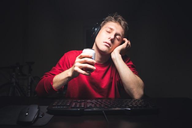 Uomo seduto a casa vicino a un computer con una lattina di bevande nelle mani e dormire