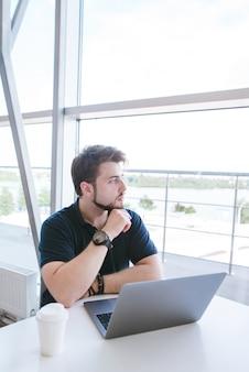 Uomo seduto a un tavolo da coworking con un bicchiere di caffè e guardando nella finestra con una bellissima vista