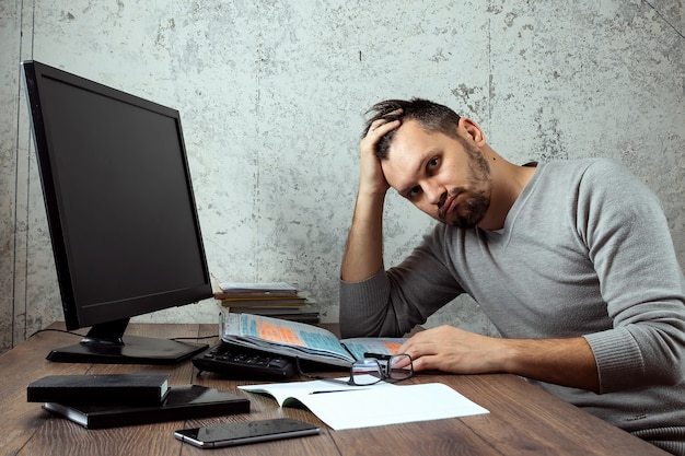 Uomo seduto a un tavolo in ufficio e non funzionante, sguardo stanco.