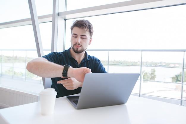 Uomo seduto a un tavolo vicino a una finestra con un computer portatile e un caffè e guardando il suo orologio
