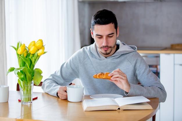Uomo seduto al tavolo con una tazza di caffè o tè e mangiare croissant.