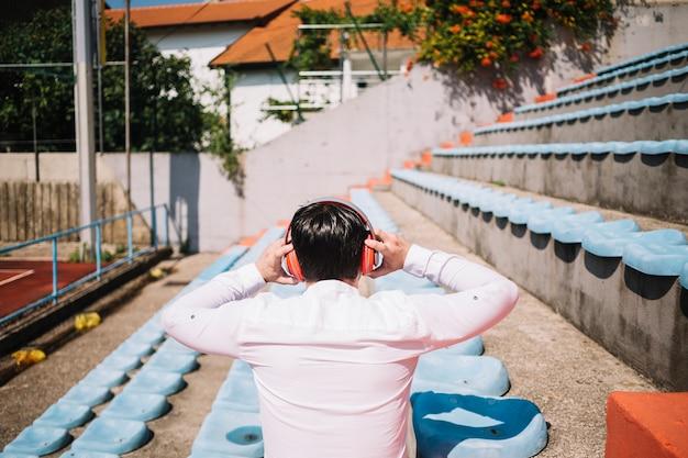Uomo seduto con gli auricolari