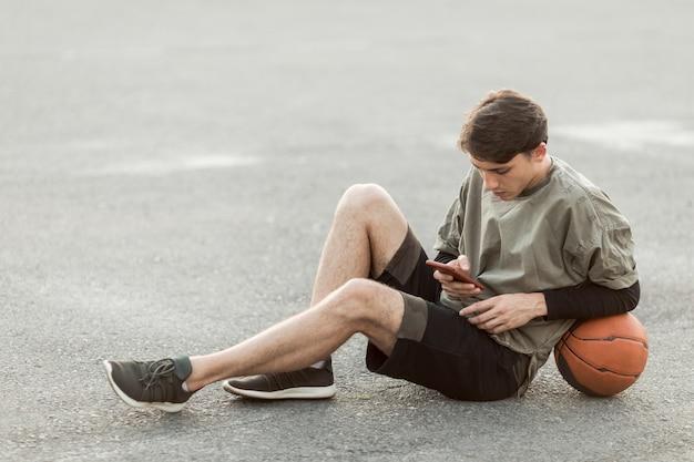 Uomo seduto con un pallone da basket