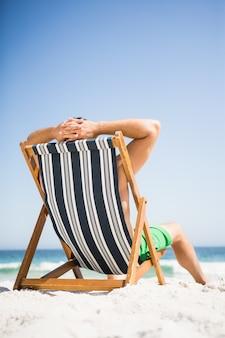 Uomo seduto e rilassante sulla sedia a sdraio