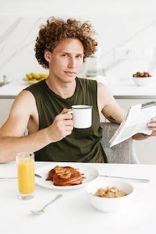 Uomo seduto in cucina mentre si tiene il giornale