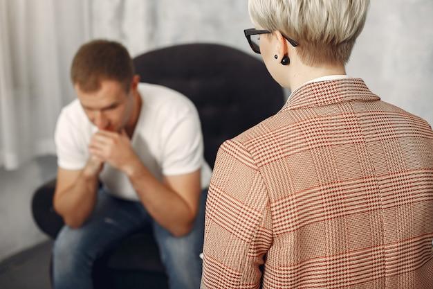 Uomo seduto nell'ufficio dello psicologo e parlando di problemi