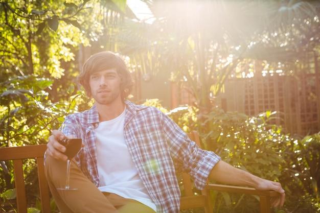Uomo seduto su una panchina con un bicchiere di vino rosso in giardino