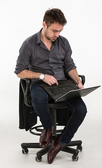 Uomo seduto su una sedia con un computer portatile in mano. studio, sfondo bianco.
