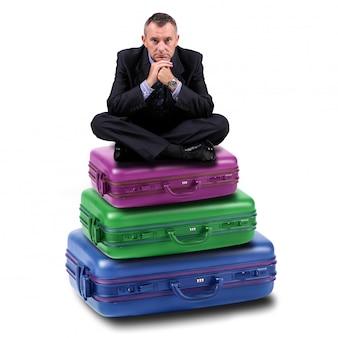 Uomo seduto su valigie