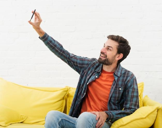 Uomo seduto sul divano e scattare selfie