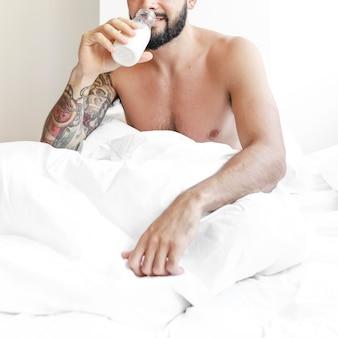 Uomo seduto sul letto a bere latte