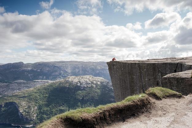 Uomo seduto sul preikestolen, pulpit rock nel bellissimo paesaggio montano della norvegia