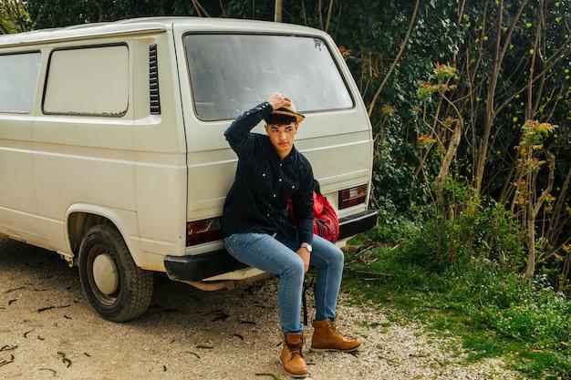 Uomo seduto sul retro del furgone che si tocca il cappello sopra la testa