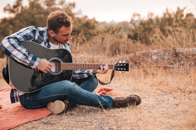 Uomo seduto sulla coperta a suonare la chitarra