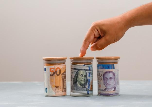 Uomo selezionando uno dei vasetti di denaro.