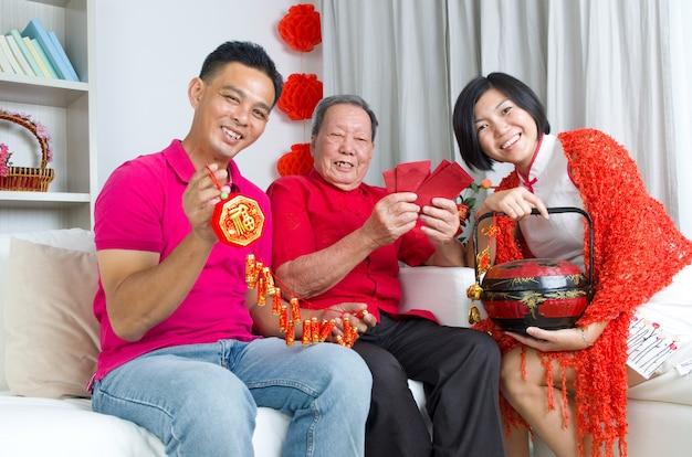 Uomo senior asiatico e bambini che celebrano nuovo anno cinese