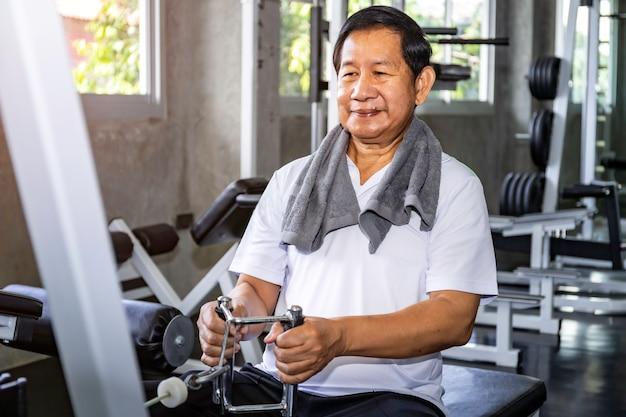 Uomo senior asiatico nell'addestramento degli abiti sportivi con la macchina alla palestra.
