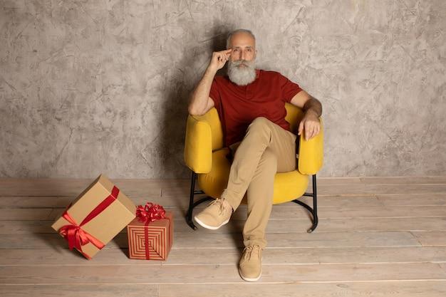 Uomo senior barbuto con un contenitore di regalo su fondo grigio.