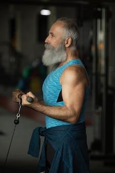 Uomo senior barbuto in abbigliamento sportivo in palestra che risolve con i pesi.