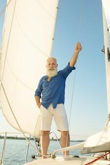 Uomo senior barbuto sulla barca a vela o sull'yacht che galleggia sul lago.