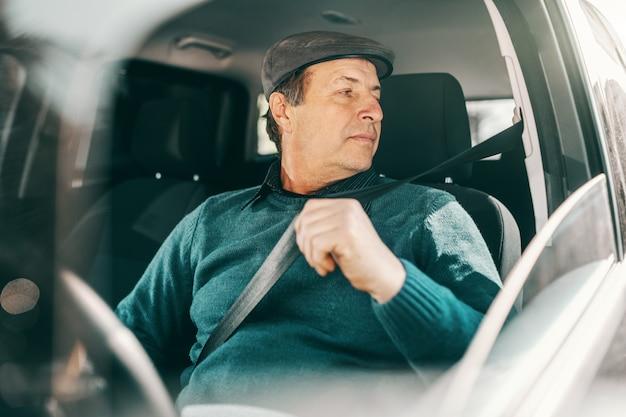 Uomo senior caucasico serio con la protezione sulla testa che si siede in automobile e che allaccia la cintura di sicurezza