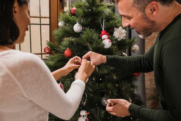 Uomo senior che aiuta sua moglie con la decorazione
