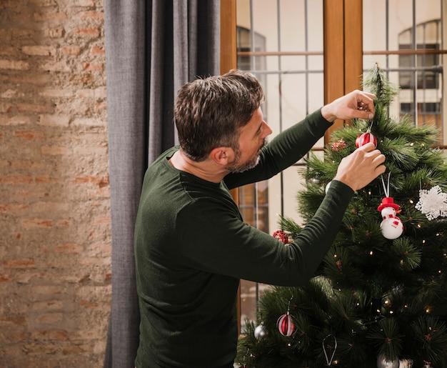 Uomo senior che decora l'albero di natale all'interno