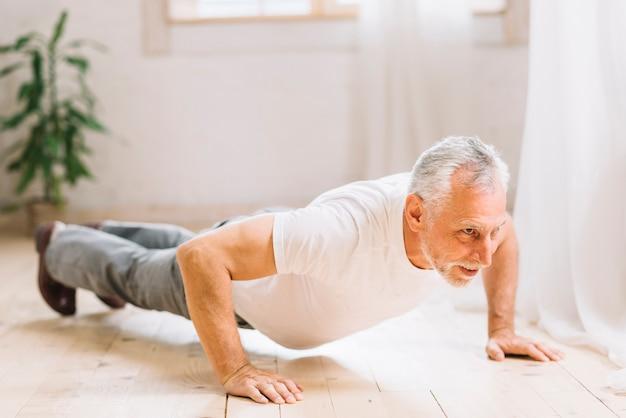Uomo senior che fa esercizio di piegamento sulle braccia sul pavimento di legno duro