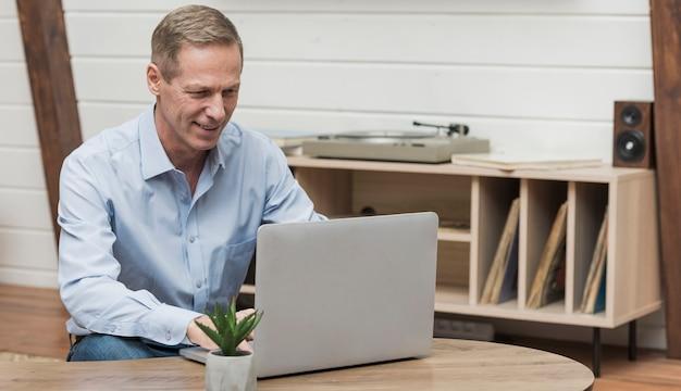 Uomo senior che guarda attraverso internet