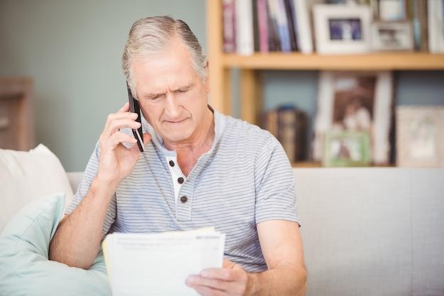 Uomo senior che per mezzo del telefono cellulare mentre guardando i documenti