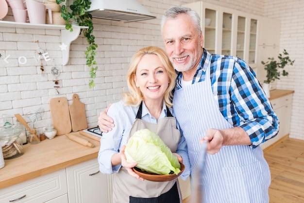 Uomo senior che prende selfie con sua moglie che tiene cavolo in piatto