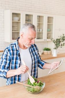 Uomo senior che prepara l'insalata osservando ricetta sulla compressa digitale nella cucina