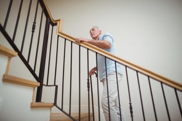 Uomo senior che scala di sopra con il bastone da passeggio