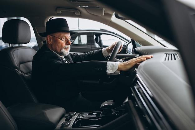 Uomo senior che si siede dentro un'automobile