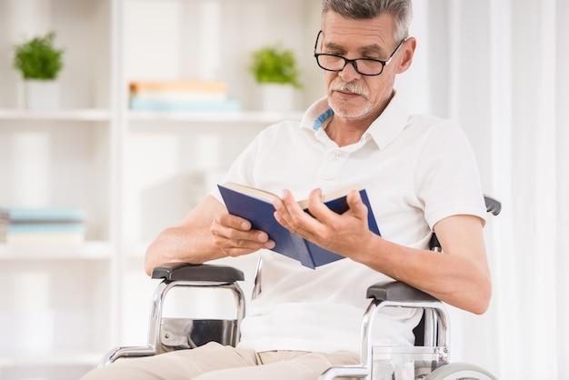 Uomo senior che si siede in sedia a rotelle e che legge un libro a casa.