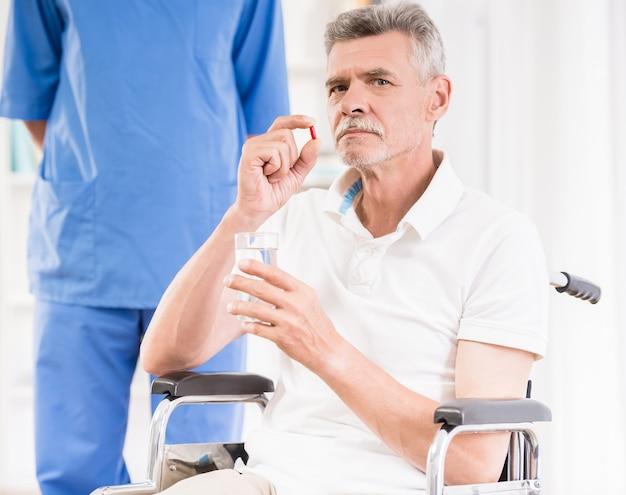 Uomo senior che si siede in sedia a rotelle e che prende le pillole.