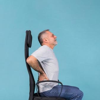 Uomo senior che si siede in sedia che ha dolore alla schiena su fondo blu