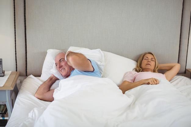 Uomo senior che si trova sul letto e che copre le sue orecchie di cuscino