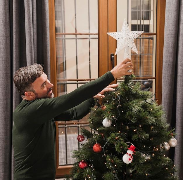 Uomo senior che sistema la stella sull'albero di natale