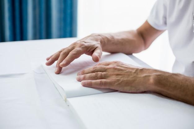 Uomo senior che usando il braille per leggere