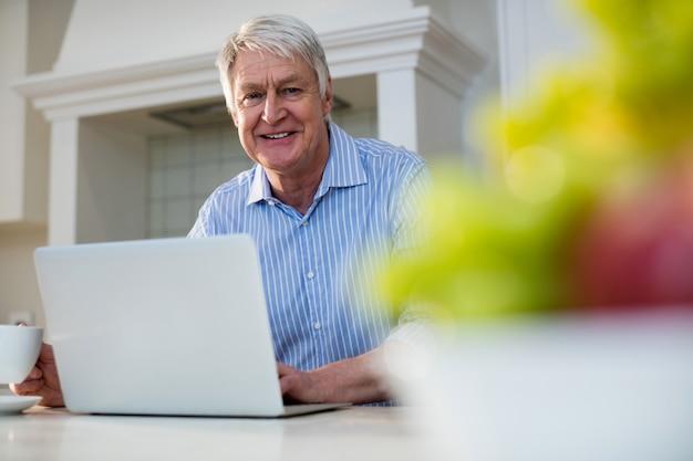 Uomo senior che utilizza computer portatile nella cucina
