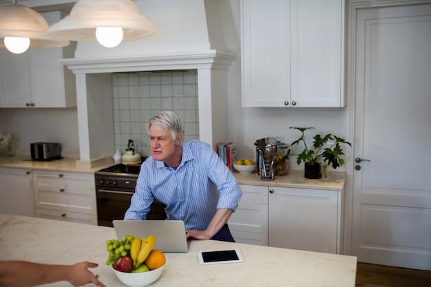 Uomo senior che utilizza interazione mentre usando computer portatile nella cucina