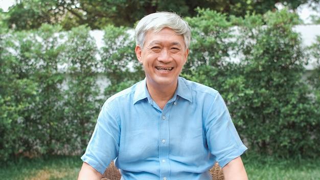 Uomo senior cinese asiatico del ritratto che ritiene sorridere felice a casa. il maschio più anziano si rilassa il sorriso a trentadue denti che guarda mentre si trova nel concetto del giardino a casa di mattina.