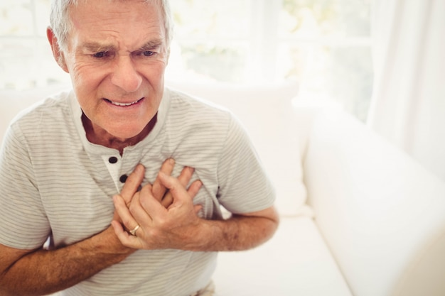 Uomo senior con dolore sul cuore in camera da letto