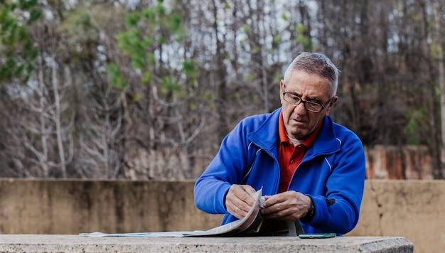Uomo senior con i vetri che legge giornale al parco