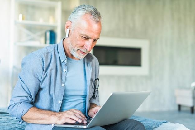 Uomo senior con il bluetooth senza fili che si siede sul letto facendo uso del computer portatile