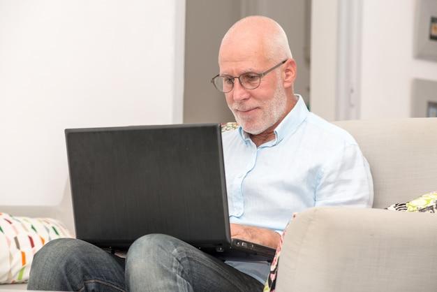 Uomo senior con il computer portatile che si siede in sofà